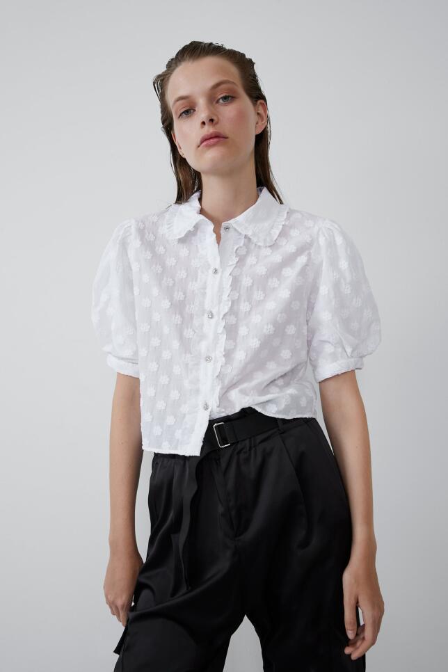 Las blusas románticas de color blanco son perfectas para estrenar ahora mismo. Blusa con botón joya de Zara 22,95 EUR